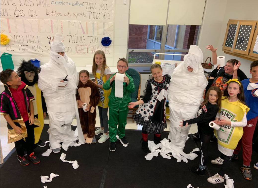 Principal Sedlak and teacher Yvonne Hayes are wrapped up as mummies with 5th grade students.