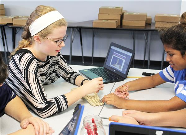 Students work together to find the proper tension to make the prosthetic hand function.
