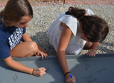 Photo of MIddle School students signing a steel beam.